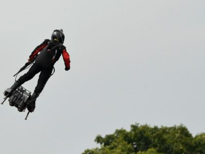 A man on flying board soars over the mob during Bastille Day Celebrations